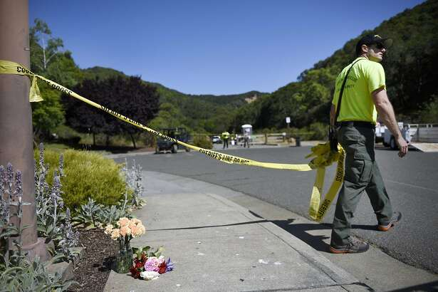 Bradley Haas, a volunteer with the Marin County Sheriff's Search and Rescue Team strings up a line of police tape near a small vase of flowers left in memorial near the start of a trail head on the Indian Valley Preserve which was the scene of a double shooting involving students from Navato High School in Novato, CA Thursday, May 26th, 2016.