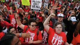 Protesters converge at the McDonald's campus in Oak Brook, Ill., on Thursday to rally for a $15 per hour work wage during the annual shareholders meeting.