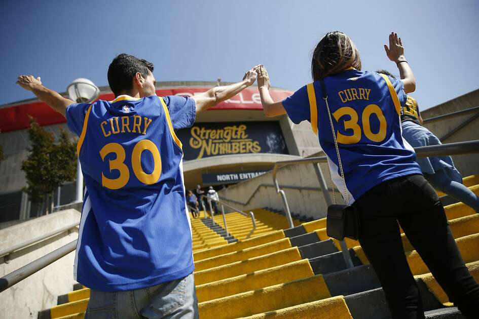 Golden State Warriors' fans Edgar and Jozelyn Reyes make a W while being photographed before Warriors play Oklahoma Thunder in Game 5 of NBA Playoffs' Western Conference Finals at Oracle Arena in Oakland, Calif., on Thursday, May 26, 2016.