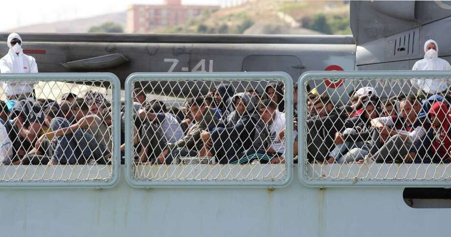 Migrants wait to disembark on Thursday from the Italian Navy ship Bettica as it arrives at the Sicilian Porto Empedocle harbor. Coast guards in Italy and Libya rescued over 4,000 people Thursday, setting a record.  Photo: Francesco Malavolta, STR / Copyright 2016 The Associated Press. All rights reserved. This material may not be published, broadcast, rewritten or redistribu
