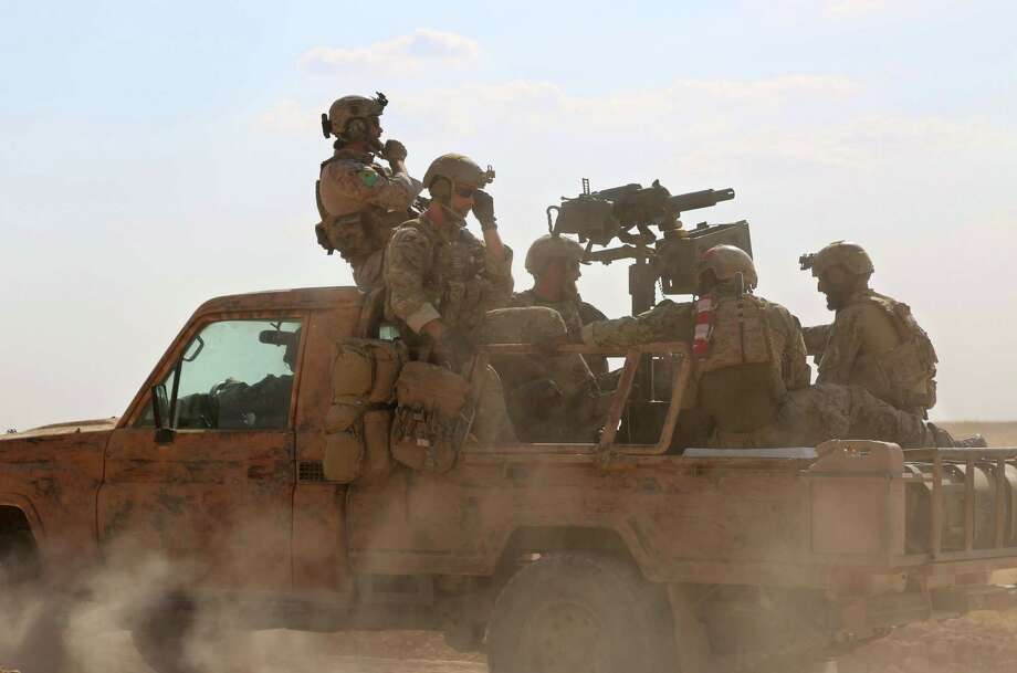 Armed men identified by Syrian Democratic Forces as U.S. special operations forces ride in the back of a pickup in the village of Fatisah in the northern Syrian province of Raqqa on Wednesday. Photo: DELIL SOULEIMAN, Stringer / AFP or licensors