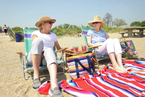 Gail Megura, left, and Karen Peterson, both of Trumbull, enjoy the afternoon at Jennings Beach in Fairfield on Wednesday. The two are longtime friends.