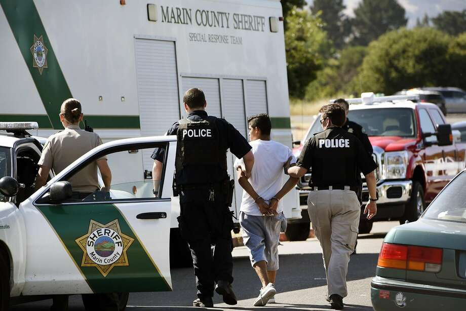 Members of the Marin County Sheriff's Office take a suspect out of a squad car for a search of his person following a raid on the Leafwood Arms apartment building on Leafwood Heights in Novato, Calif., Thursday, May 26, 2016. Photo: Michael Short, Special To The Chronicle