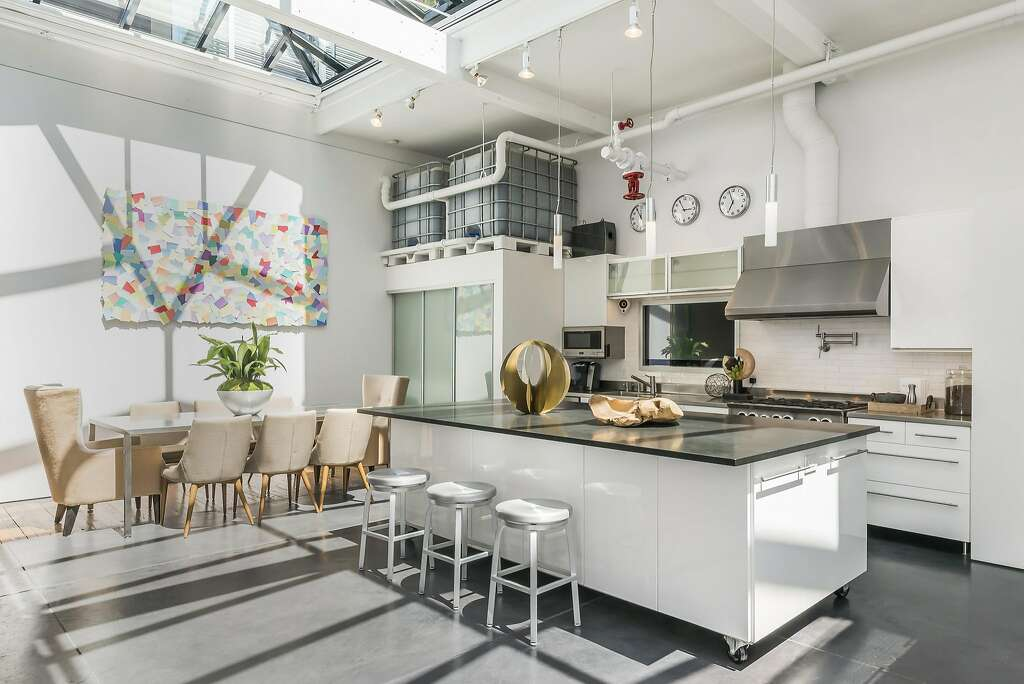 The open kitchen hosts commercial appliances and a movable island topped with honed granite. Photo: Olga Soboleva / Vanguard Properties