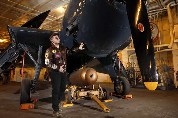 """George Retelas, 36, on May 13,2016, stands next to an Grumman TBF Avenger -carrier-borne torpedo bomber which his grandfather maintained as a aircraft mechanic aboard the aircraft carrier USS Hornet in Alameda, California. Retelas a photographer inherited his grandfather's Graflex large format camera and hidden inside the camera bag was a journal from service as a aircraft mechanic in the Pacific in World War Two. Retelas tracked down survivors of Squadron 11, all in their 90s, and has made a documentary film, called """"Eleven."""""""