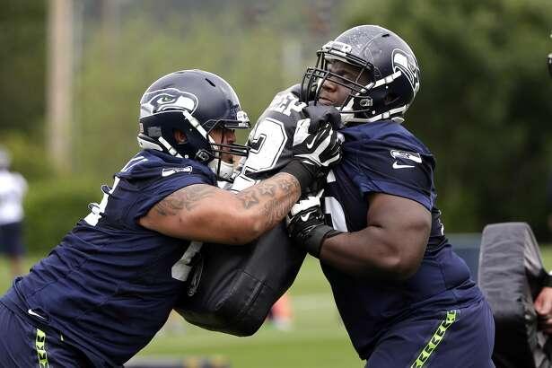 Seattle Seahawks' Germain Ifedi, right, and Kona Schwenke run through a drill at NFL football practice Thursday, May 26, 2016, in Renton, Wash. (AP Photo/Elaine Thompson)