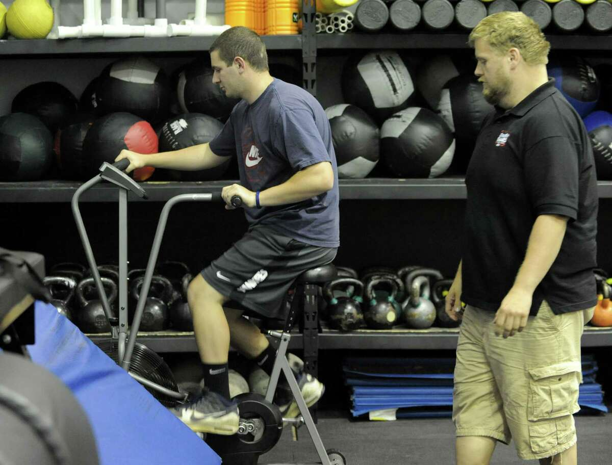 Phil D'Abbraccio warms up on a stationary bike in a CrossFit workout with a trainer Jason Murphy at Albany CrossFit which is located in The Court Club on Thursday, June 27, 2013 in Colonie, N.Y. (Lori Van Buren / Times Union)