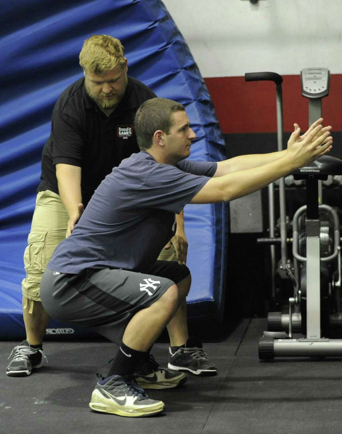 Phil D'Abbraccio performs air squats in a CrossFit workout with a trainer Jason Murphy at Albany CrossFit which is located in The Court Club on Thursday, June 27, 2013 in Colonie, N.Y. (Lori Van Buren / Times Union)