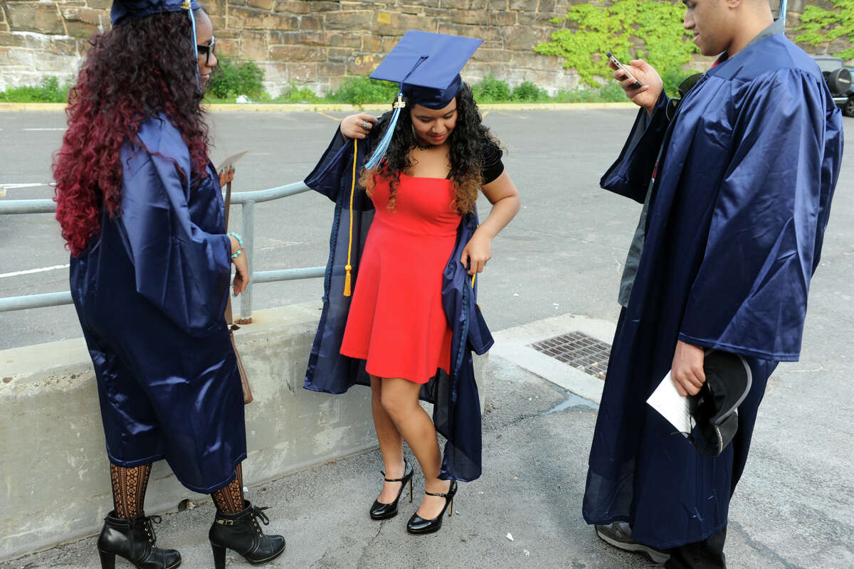 Batzabeth Castro, of Bridgeport, puts on her graduation gown prior to Housatonic Community College's 49th Commencement, held at the Webster Bank Arena, in Bridgeport, Conn. May 26, 2016.