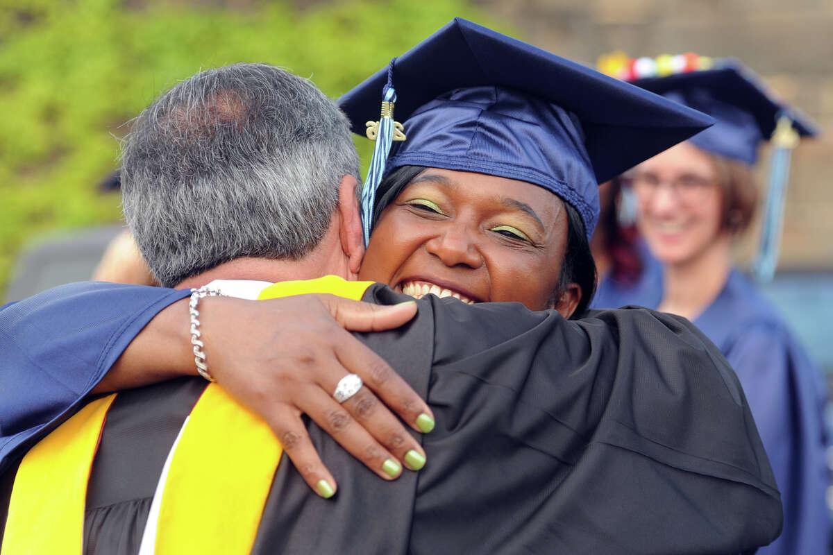 Karen Dawes Francois, of Bridgeport, receives a hug at Housatonic Community College's 49th Commencement, held at the Webster Bank Arena, in Bridgeport, Conn. May 26, 2016.