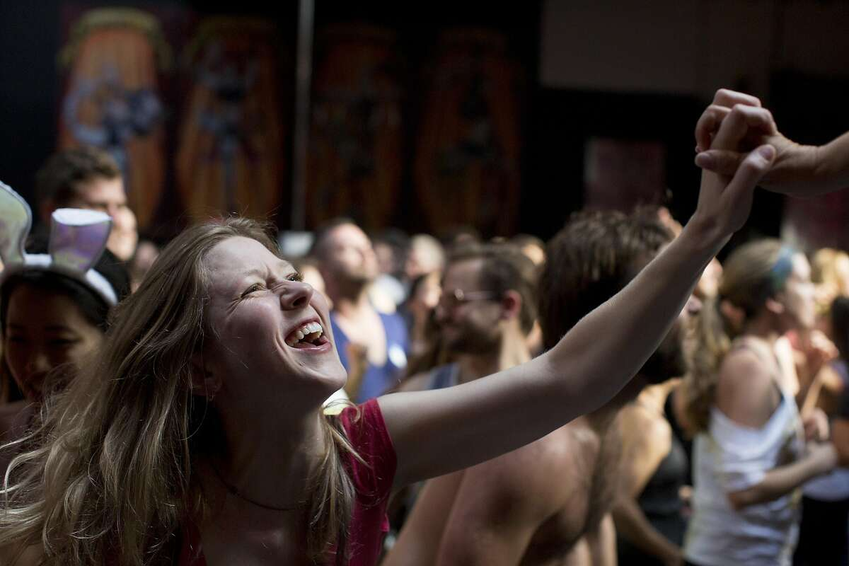Marnie Brumder grabs a dancer's hand onstage at Daybreaker, a device-free dance party hosted by Digital Detox and Camp Grounded, at Inner Mission in San Francisco, Calif. on Thursday, April 9, 2015.