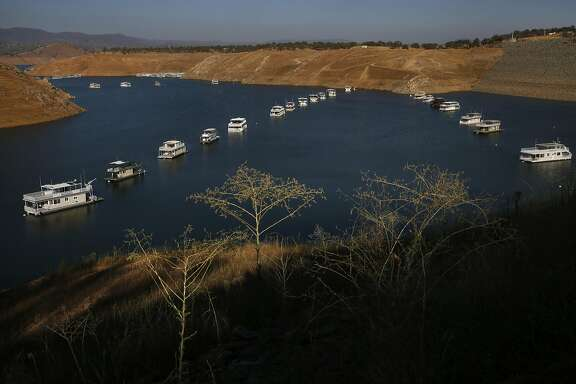 Houseboats float silently as the sun sets at Don Pedro reservoir as it hovers at 32 percent of its total capacity Aug. 19, 2015 in La Grange, Calif.