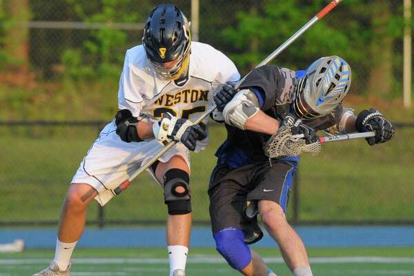 Weston's Jason Baisley (25) and Newtown's Mark Urso (10) battle for the ball in the SWC boys lacrosse championship game between Newtown and Weston high schools, on Thursday, May 26, 2016, at Newtown High School, Newtown, Conn.