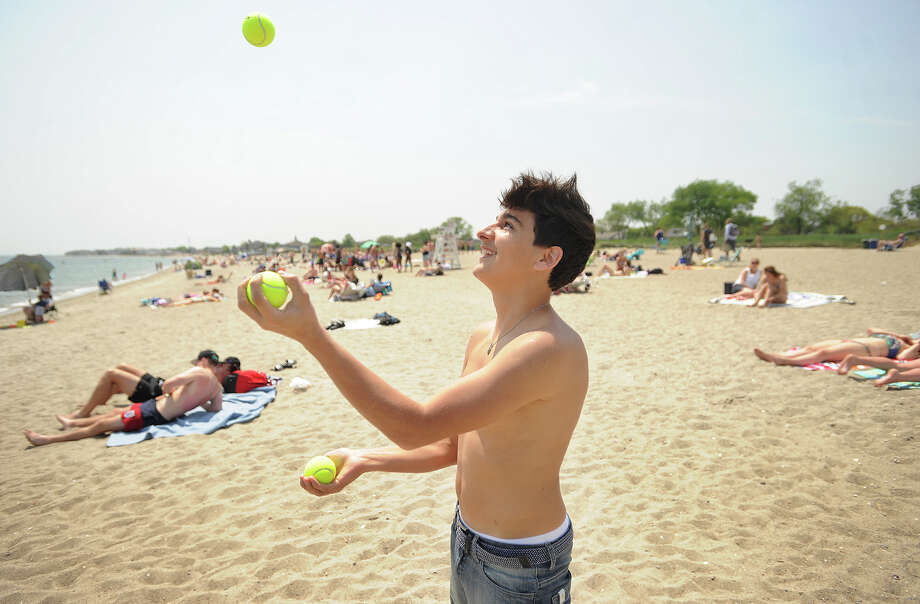 Enjoying his first visit to the beach in America, Martin Urtubey, 17, from Argentina, practices learning to juggle at Jennings Beach in Fairfield, Conn. on Wednesday, May 25, 2016. Photo: Brian A. Pounds / Hearst Connecticut Media / Connecticut Post