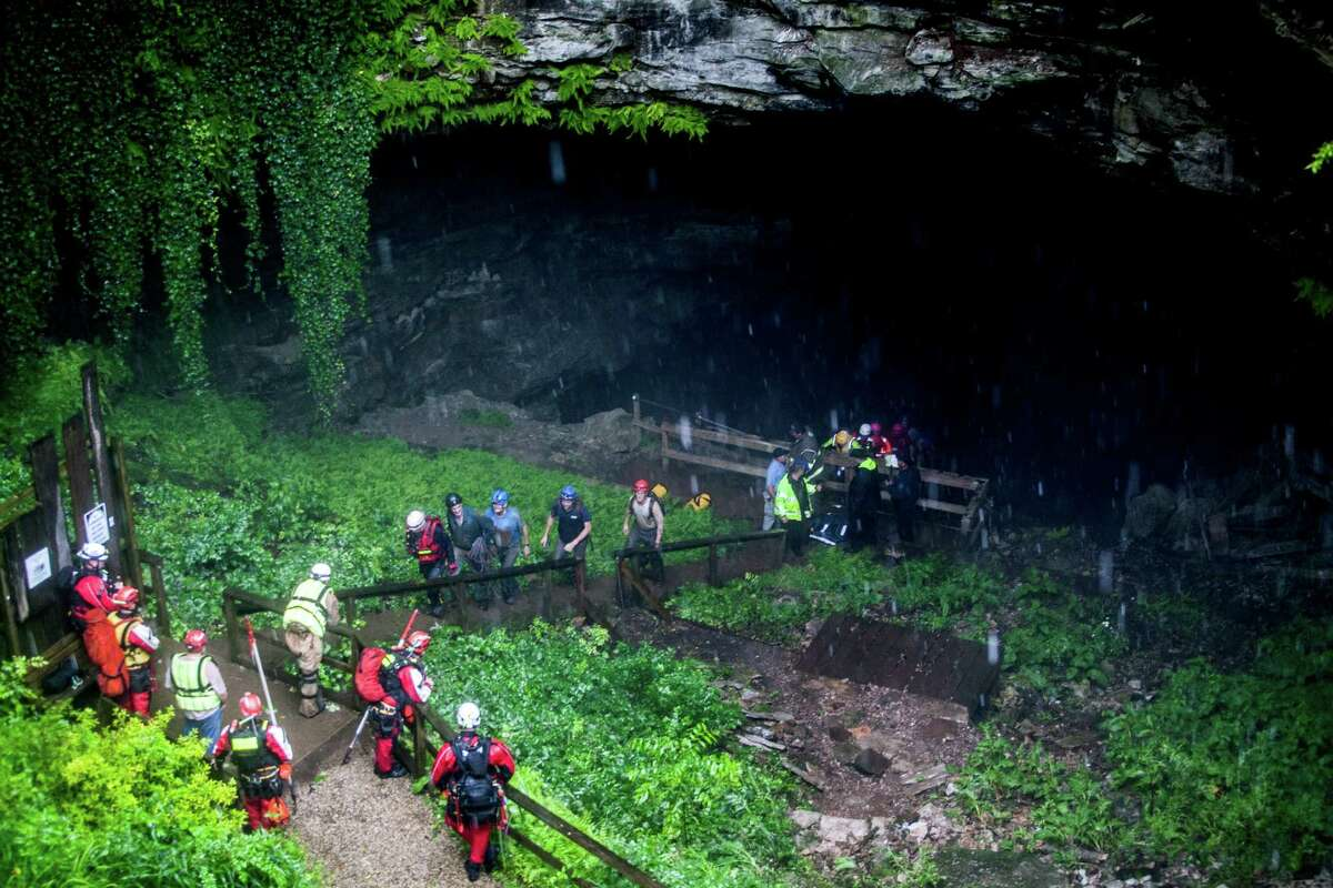 Rescued people walk out of the entrance to Hidden River Cave after officials said over a dozen people who exploring the cave were trapped by rising water Thursday, May 26, 2016, in Horse Cave, Ky. The group waded through neck-deep water to get out, authorities said Thursday. (Austin Anthony/Daily News via AP) MANDATORY CREDIT ORG XMIT: KYBOW204