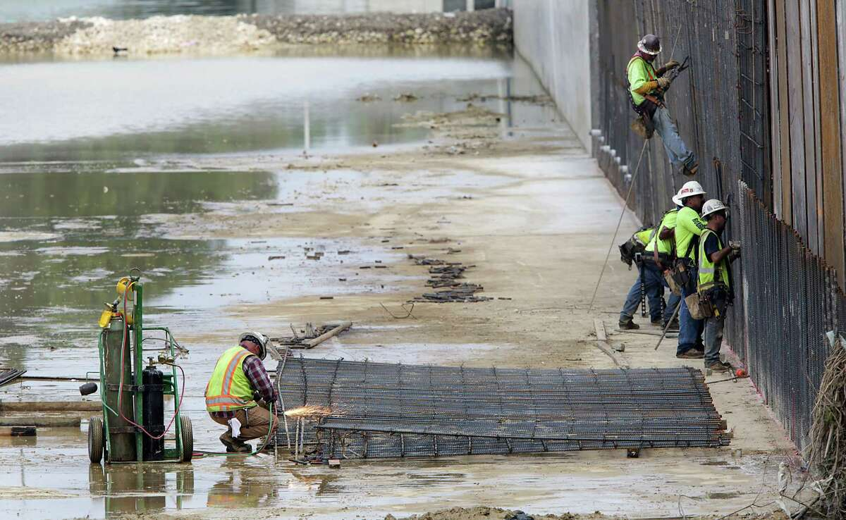 A welder prepares a reinforcement structure as other work crews work on the retaining wall during continued construction on the Seeling Channel Phase 2 Drainage Project at Wilson and Mistletoe on Thursday, May, 26, 2016.