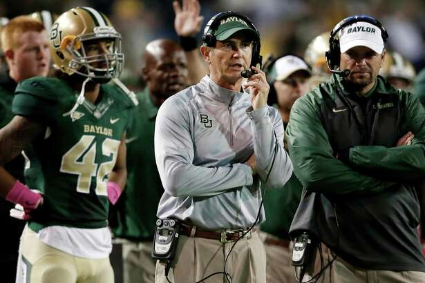 """FILE - In this Oct. 19, 2013, file photo, Baylor head coach Art Briles, center, watches during the second half of an NCAA college football game against Iowa State in Waco, Texas. Baylor University's board of regents says it will fire Briles and re-assign university President Kenneth Starr in response to questions about its handling of sexual assault complaints against players.  The university said in a statement Thursday, May 26, 2016, that it had suspended Briles """"with intent to terminate.""""  Starr will leave the position of president on May 31, but the school says he will serve as chancellor. (AP Photo/Tony Gutierrez, File)"""