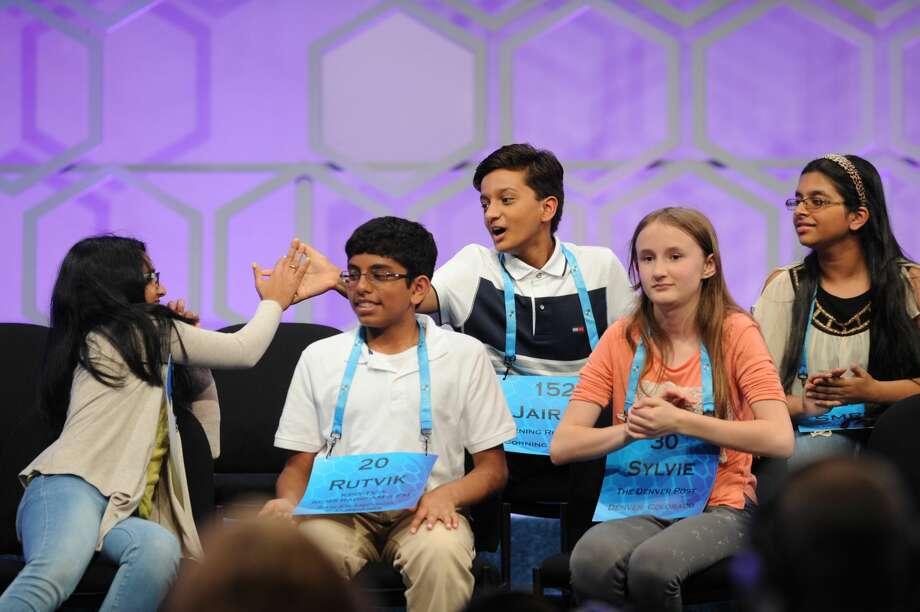 Co-champion Jairam Hathwar high-fives another finalist. Photo: Mark Bowen / Scripps National Bee