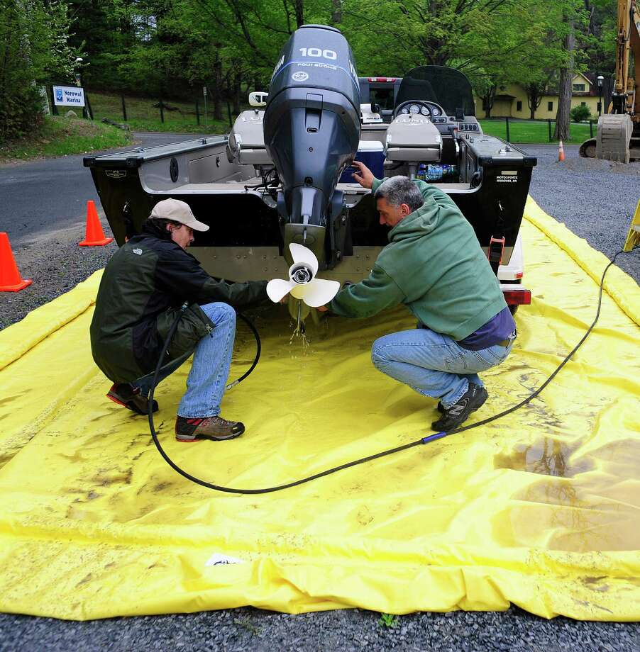 FILE — Mike Archambault, left, a vessel inspection technician checks over Carl Falco's, right, boat at Norowal Marina on Lake George on Thursday, May 15, 2014, in Bolton Landing, N.Y.  Thursday was the first day that the various regional inspection stations were operating around Lake George.  The mandatory boat inspection program is run by the Lake George Park Commission.  The purpose of the inspections are to make sure that no boats are carrying invasive species into the lake.   Boaters looking for information on the inspection sites and hours of operation can go to www.http://lgboatinspections.com. (Paul Buckowski / Times Union) Photo: Paul Buckowski / 00026911A
