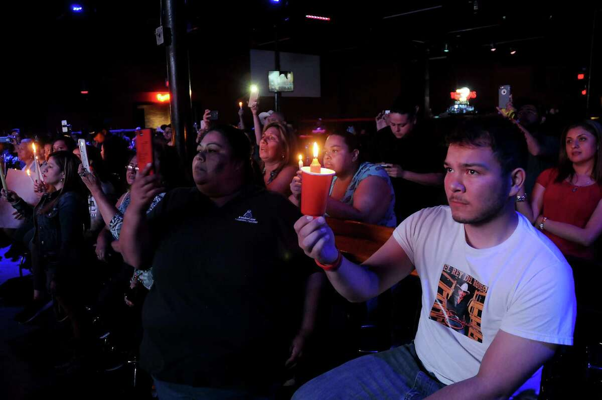 Fans hold candles at the Houston Loves Emilio candlelight vigil at the Dorado nightclub on Thursday.