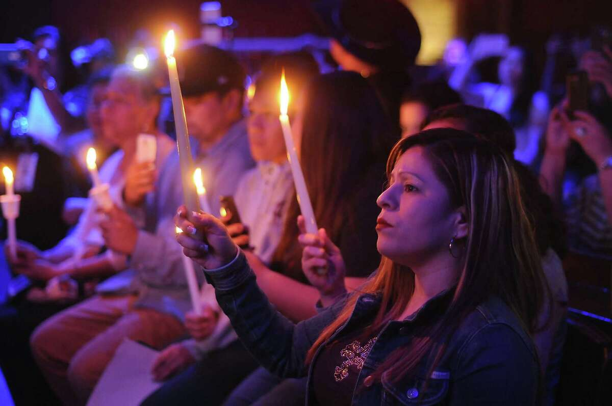 Fans hold candles at the Houston Loves Emilio candlelight vigil.