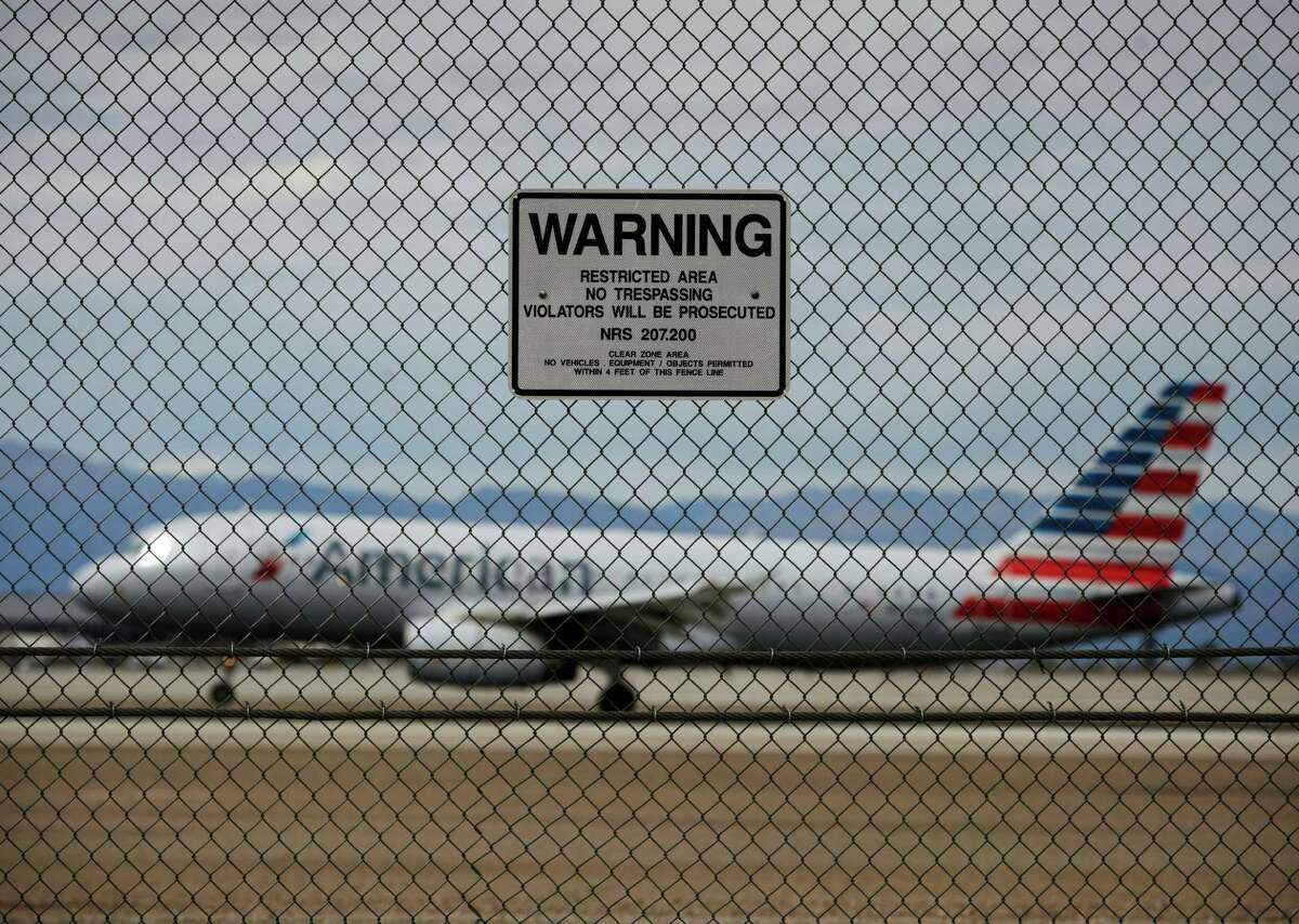 In this May 17, 2016, photo, a sign warns against trespassing as a plane lands at McCarran International Airport in Las Vegas. An Associated Press investigation has documented perimeter breaches at many of the busiest airports in the U.S. (AP Photo/John Locher) ORG XMIT: NYBZ481