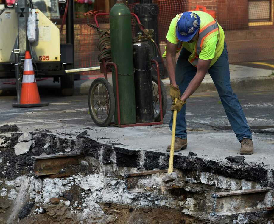 A worker removes concrete around the old trolley tracks in the sinkhole at the intersection of New Scotland and Madison Avenues  Thursday morning May 26, 2016, in Albany, N.Y.  A completion date has not been set for the repair of the large sinkhole.  (Skip Dickstein/Times Union) Photo: SKIP DICKSTEIN / 20036761A