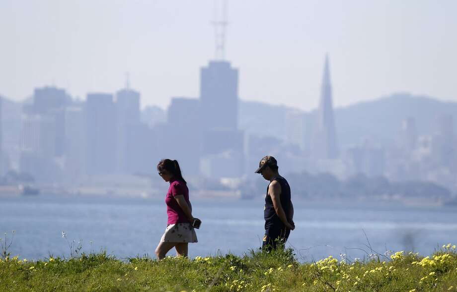 Hikers walk along the Berkeley Marina waterfront in Berkeley, Calif. on Monday, Feb. 16, 2015. The National Weather Service is forecasting sunny skies for the Bay Area through the Memorial Day weekend with temperatures ranging from the mid-60s in San Francisco to the low-90s in parts of the East Bay. Photo: Paul Chinn, The Chronicle