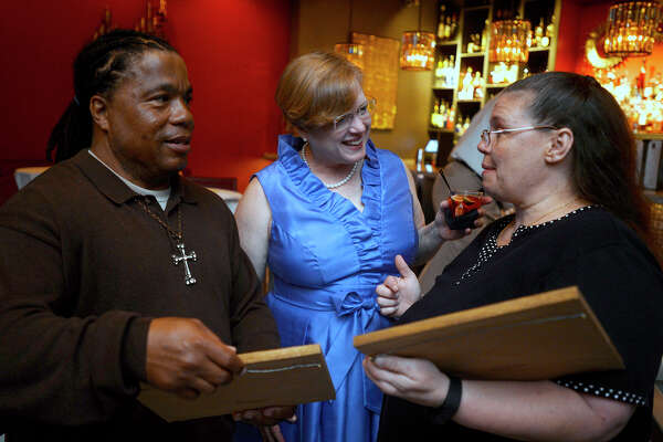 Clarence Jones, left, and Tashia Johnson, right talk with Sandee Wagner after receiving house keys during the Habitat for Humanity of Jefferson County's 40th anniversary party at Portus Lounge on Thursday. Photo taken Thursday 5/26/16 Ryan Pelham/The Enterprise
