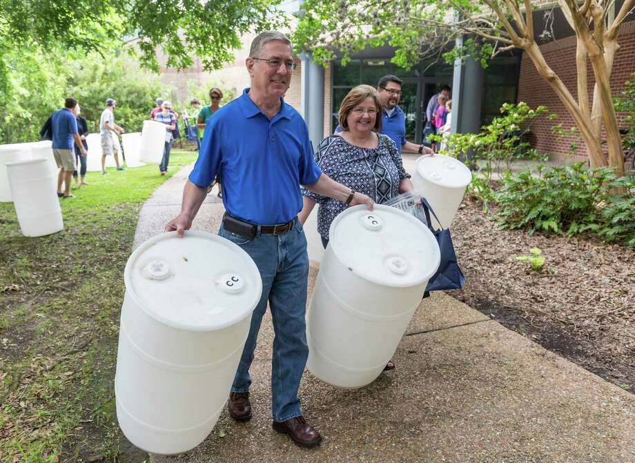 Bruce and Jana Coogler take home two 35-gallon barrels for collecting rainwater after attending a rain barrel workshop at the Houston Zoo. Photo: Craig Hartley, Freelance / Copyright: Craig H. Hartley