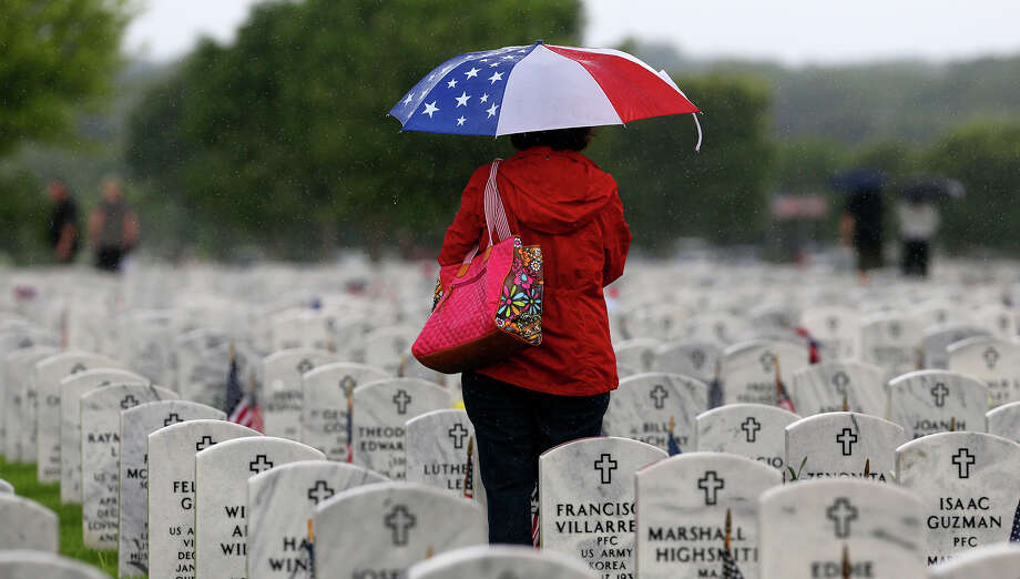 Janie Ramos tvisits her father's grave after the Memorial Day ceremony Monday May 25, 2015 at Fort Sam Houston National Cemetery. Her father, Joe J. Ramos, served in the Army during World War II. Photo: John Davenport, Staff / San Antonio Express-News / ©San Antonio Express-News/John Davenport