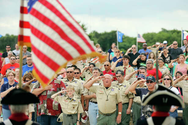 People salute during the Pledge of Allegiance Friday May 22, 2015 at Fort Sam Houston National Cemetery. About 1000 Boy Scouts, Girl Scouts and others placed American flags on graves to honor members of the military for Memorial Day.