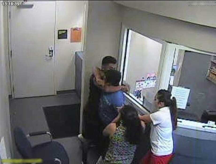 Three bystanders restrain a man armed with a razor blade in the Mount Pleasant Municipal Court building on May 27, 2016.