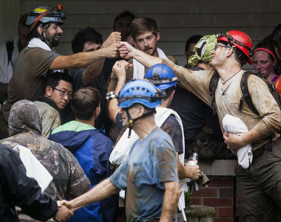 Those who were rescued from Hidden River Cave celebrate on Thursday after escaping the rising waters. In all, 19 people managed to get out of the cave unharmed after a flash flood threatened to drown them. Photo: Austin Anthony, Associated Press