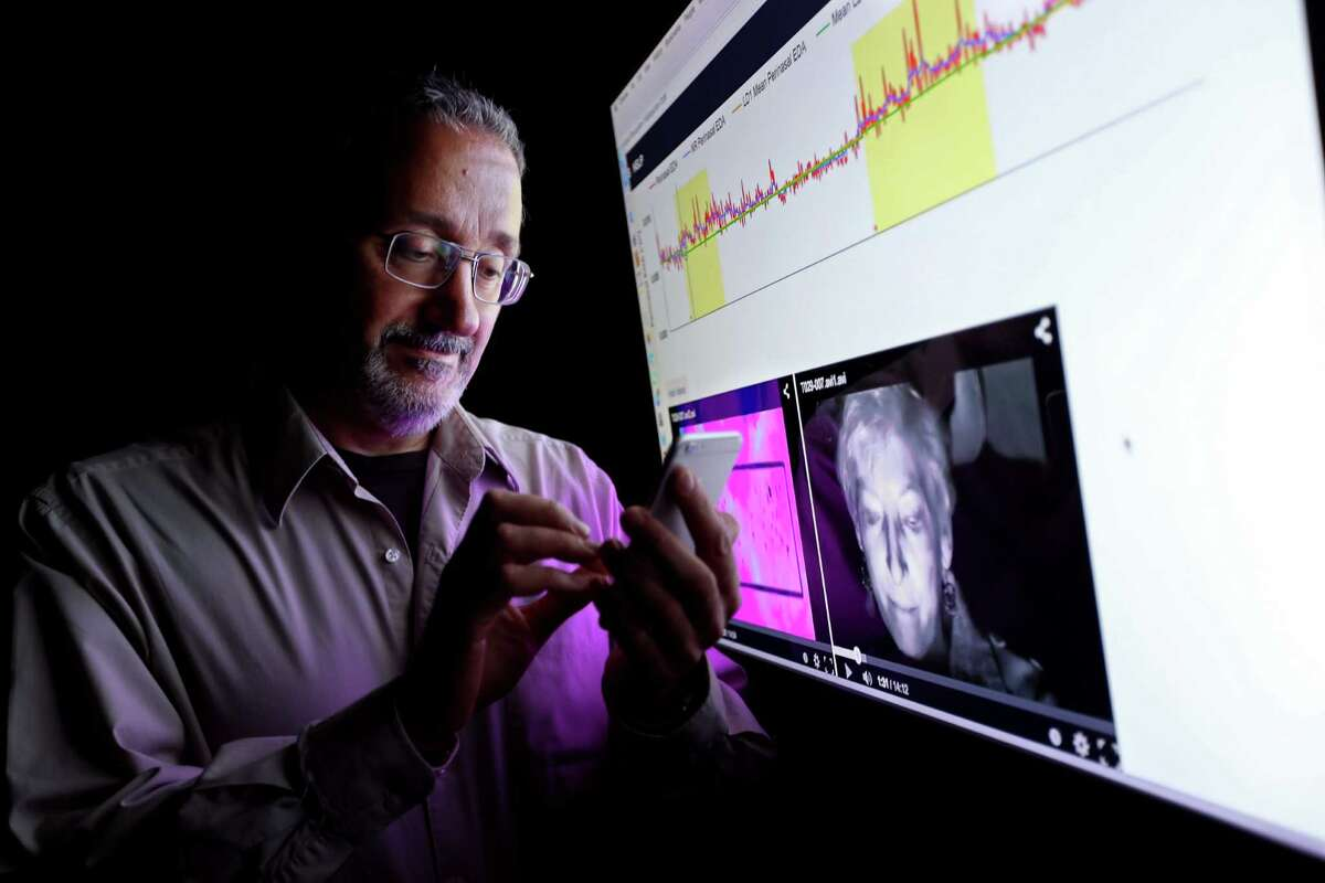 University of Houston computer science professor Ioannis Pavlidis types on his cell phone May 13, as some of the data from a recent test of stress on drivers is shown on a monitor.