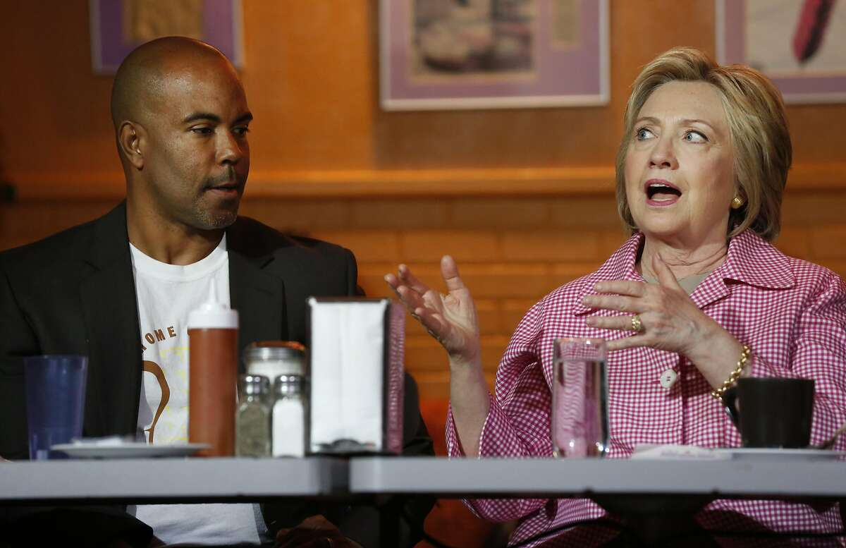 Presidential candidate Hillary Clinton, right, chats with the Owner of Home of Chicken and Waffles Derreck Johnson about a program he has at his restaurant that employs those on parole or probation during a community meeting in the Home of Chicken and Waffles May 27, 2016 in Oakland, Calif. Clinton met with Mayor Schaaf and other community members to discuss local issues.