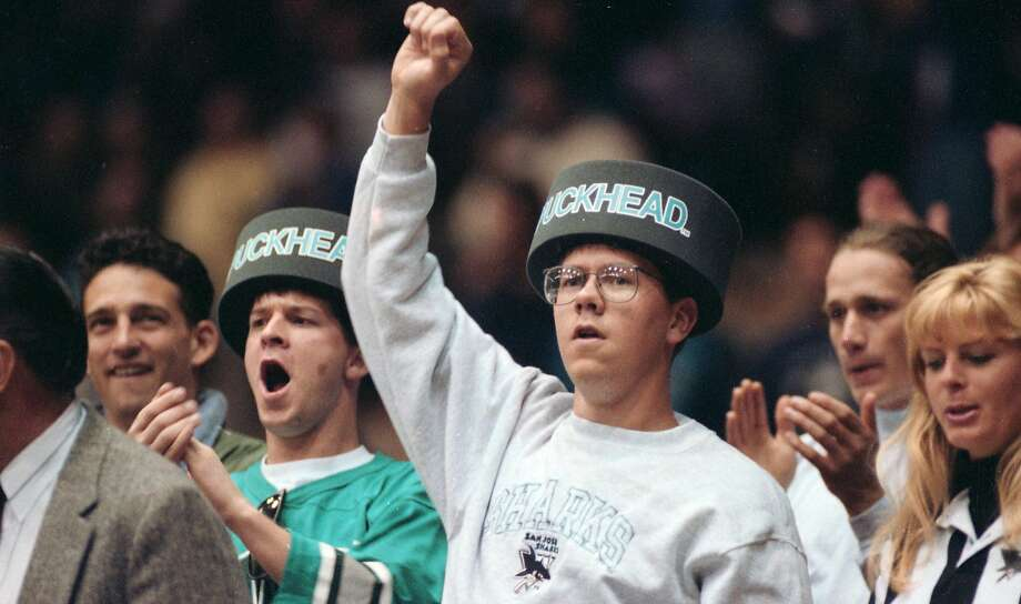 """April 4, 1993: Two fans wear """"Puckhead"""" hats during the national anthem at a Sharks game at the Cow Palace in Daly City. Photo: Brant Ward, The Chronicle"""