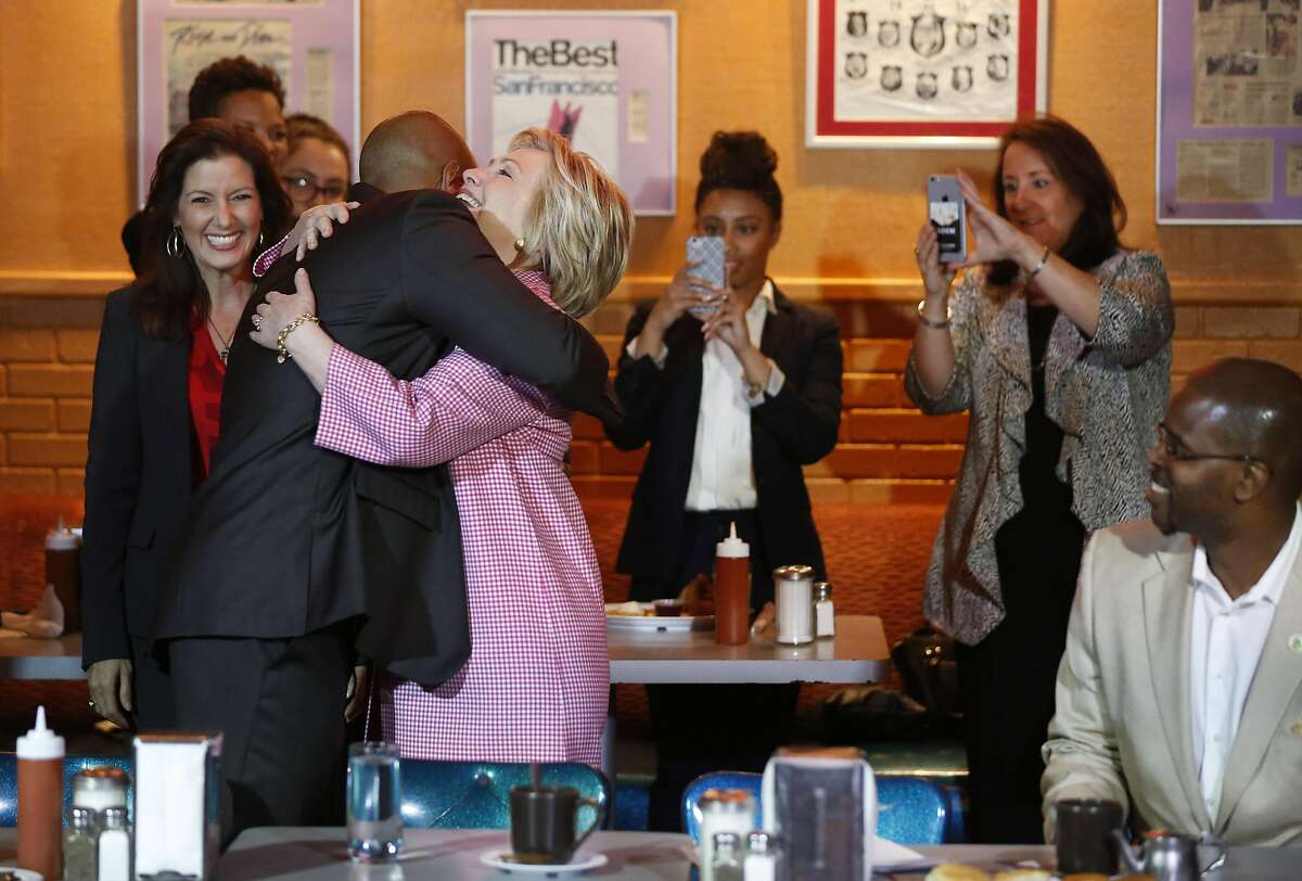 Presidential candidate Hillary Clinton hugs the Owner of Home of Chicken and Waffles Derreck Johnson after meeting him in his restaurant the Home of Chicken and Waffles for a community leaders meeting May 27, 2016 in Oakland, Calif. Clinton met with Mayor Schaaf and other community members to discuss local issues.