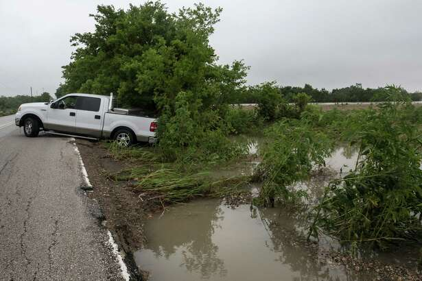 A pickup truck, that was washed off of Von Quintus Road during overnight flooding, rests on the side of the road in southeast Travis County, Friday, May 27, 2016, near Austin, Texas, on Friday, May 27, 2016.  (Rodolfo Gonzalez/Austin American-Statesman via AP)