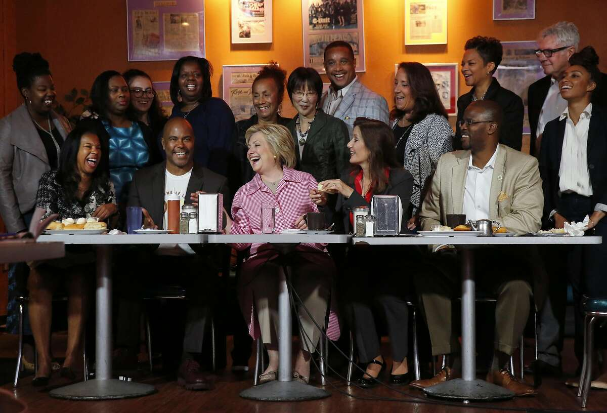 Presidential candidate Hillary Clinton, center, jokes with community leaders and members, from left, Regina Jackson, CEO of East Oakland Youth Development Center, Derreck Johnson, Owner of Home of Chicken and Waffles, Alameda County Supervisor Wilma Chan, (standing) Mayor Libby Schaaf, OSUSD Superintendent Antwan Wilson as they all prepare to pose for a photograph after a meeting in the Home of Chicken and Waffles May 27, 2016 in Oakland, Calif. Clinton met with Mayor Schaaf and other community members to discuss local issues.