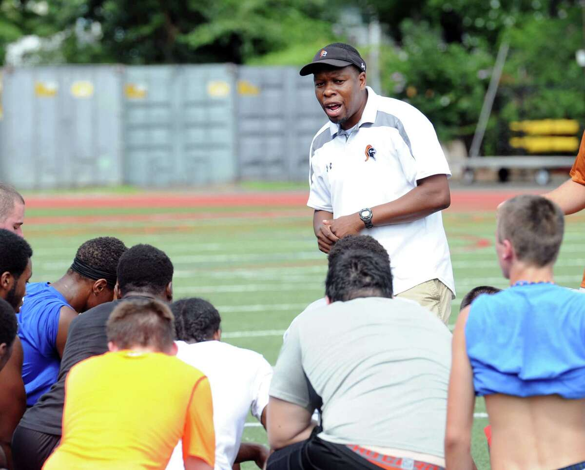 Stamford High School football coach Jamar Greene speaks with his team during the first day of football practice at the school in Stamford, Conn., Friday, Aug. 21, 2015.