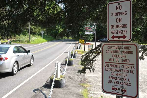 No parking signs at the entrance to a business on Route 39 near Squantz Pond State Park in New Fairfield. When the parking lot is at capacity the state closes the park to cars, but still allows walk-ins. That has become a concern for the town of New Fairfield. People are parking around town and walking to the park on roads with no shoulders.