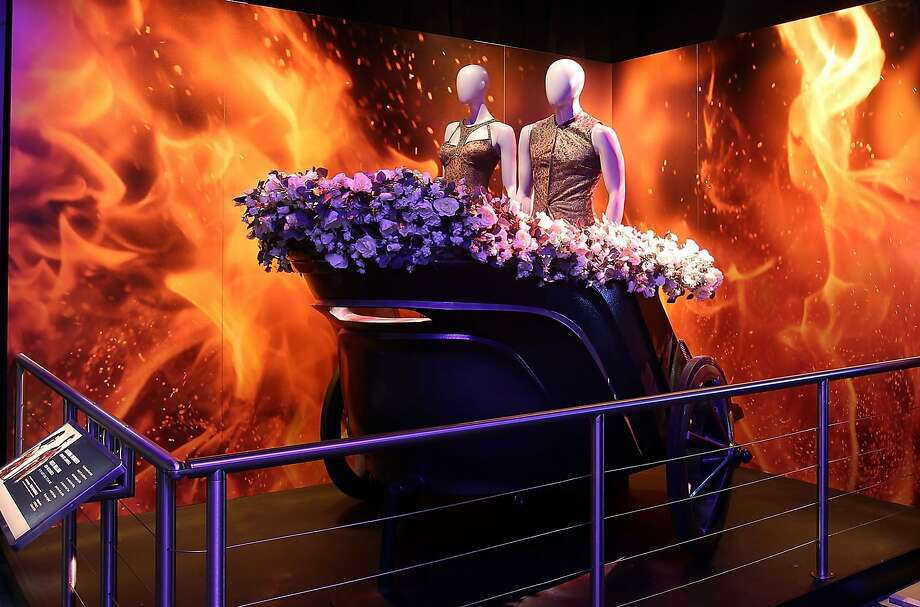 "Katniss Everdeen and Peeta Mellark ride a chariot in the tributes parade in ""The Hunger Games: Catching Fire,"" part of ""The Hunger Games: The Exhibition."" Photo: Hunger Games: The Exhibition"