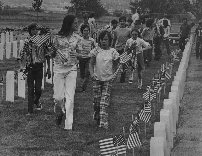 MAY 24 1974, MAY 25 1974; Youngsters Decorate Fort Logan Graves Friday; Young Denverites head out into Fort Logan National Cemetery after picking up U.S. flags for the traditional Memorial Day decoration of the graves Friday afternoon. The youngsters are all sixth and seventh grade pupils at Denver's Traylor Elementary School, 2900 S. Ivan Way. The youngsters put a flag on each grave in the cemetery. (Photo By Ira Gay Sealy/The Denver Post via Getty Images)