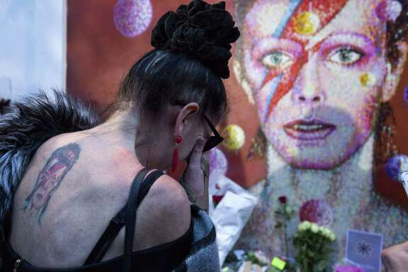 "A woman with a tatoo of David Bowie reacts as she pays her respects in front of the British singer, painted by Australian street artist James Cochran, aka Jimmy C, following the announcement of Bowie's death, in Brixton, south London, on January 11, 2016. British music icon David Bowie died of cancer at the age of 69, drawing an outpouring of tributes for the innovative star famed for groundbreaking hits like ""Ziggy Stardust"" and his theatrical shape-shifting style."
