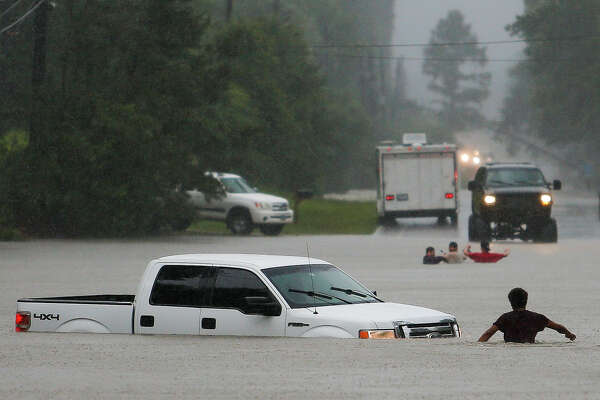 A man checks to make sure everyone made it safely out of a truck that flooded when the three men in the background drove around a road barrier on Nichols Sawmill Road in Magnolia and lost control of the vehicle in the water.
