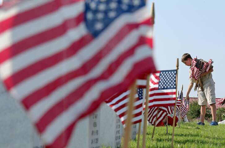 Troop 51 Boy Scout Parker Menck, 12, places American flags at the headstones of fallen service members Friday May 27, 2016 at Fort Sam Houston National Cemetery.  Over 1,000 local Boy Scouts, Girl Scouts, and others participated in the annual tradition to honor fallen service members the Friday before Memorial Day.