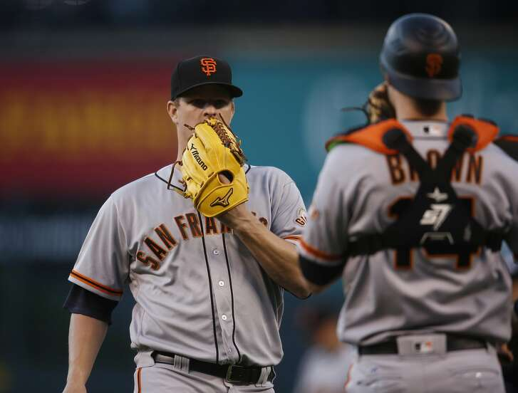 San Francisco Giants starting pitcher Matt Cain, back, confers with catcher Trevor Brown while facing Colorado Rockies' Nolan Arenado in the first inning of a baseball game Friday, May 27, 2016, in Denver. (AP Photo/David Zalubowski)