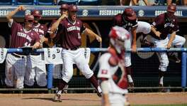 Texas A&M's Corbin Martin (center) celebrates with his teammates outside of the dugout the Aggies scored against South Carolina in the second inning at the Southeastern Conference tournament on May 26, 2016, in Hoover, Ala.