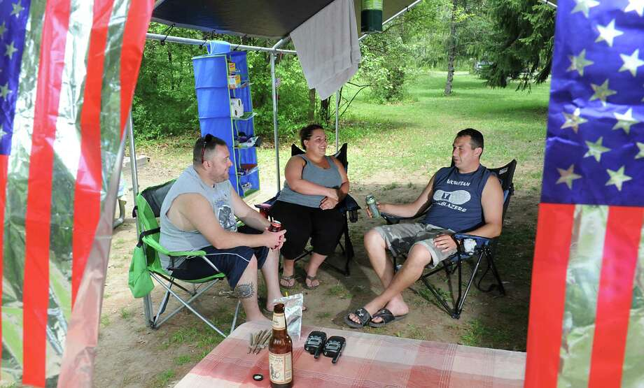 Memorial Day weekend campers, from left, Jay and Sarah Brassard of Rotterdam and Cole VanDerlinden of Burnt Hills enjoy some drinks in the shade of their canopy at Thompson's Lake State Campground on Friday, May 27, 2016 in New Scotland, N.Y. (Lori Van Buren / Times Union) Photo: Lori Van Buren / 20036771A
